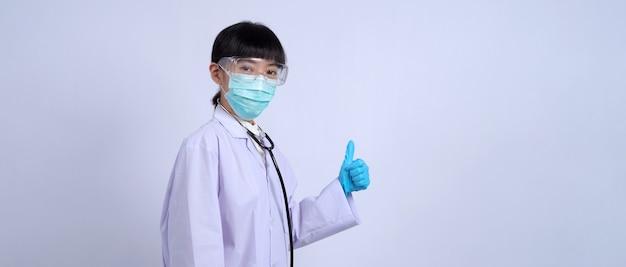 彼女の横のスペースをコピーするために指を指しているアジアの女性医師と彼女は白い色のスーツを着ています
