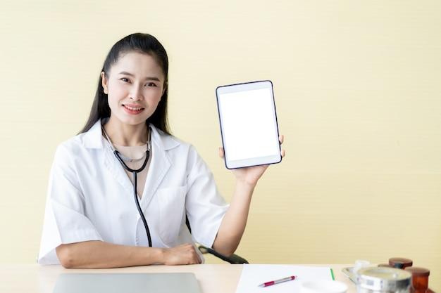 빈 흰색 화면 태블릿, maketing 및 의료 서비스 및 병원에서의 comumcication의 개념을 보여주는 아시아 여자 의사.