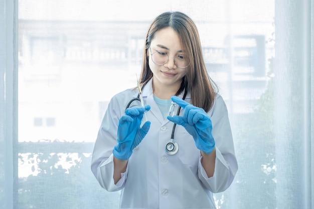 ワクチンのボトルと注射器を立って保持しているアジアの女性医師。エピデミック疾患に対する健康保護の概念。