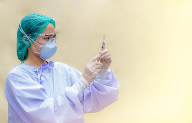 健康保護のワクチンボトルと注射器の概念を立って保持しているアジアの女性医師