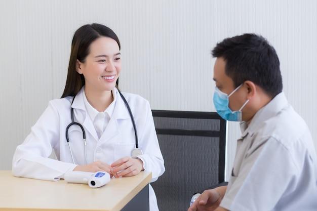 아시아 여성 의사는 남자 환자와 이야기하고 병원에서 자신의 건강을 돌보도록 격려합니다.