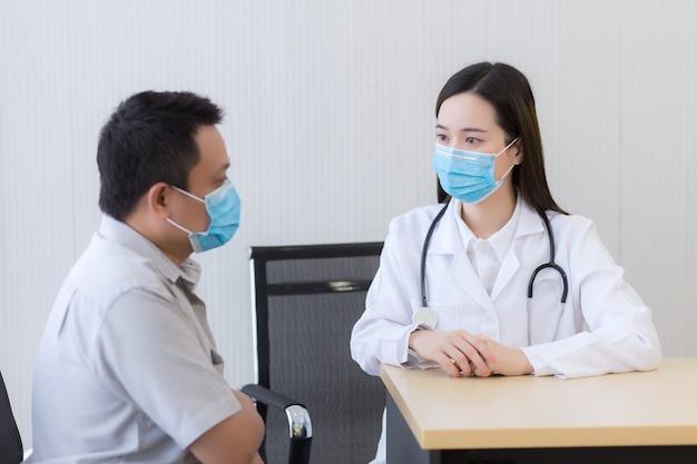 그의 고통과 증상에 대해 남자 환자와 이야기하는 아시아 여자 의사