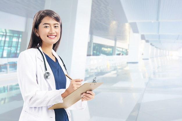 Asian woman doctor in white lab coat and stethoscope holding clipboard