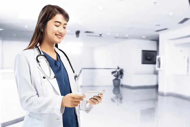 Asian woman doctor in white lab coat and stethoscope using tablet