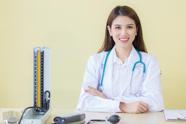 웃는 얼굴을 한 아시아 여성 의사는 병원 탁자에 혈압계가 있는 사무실에 앉아 있다