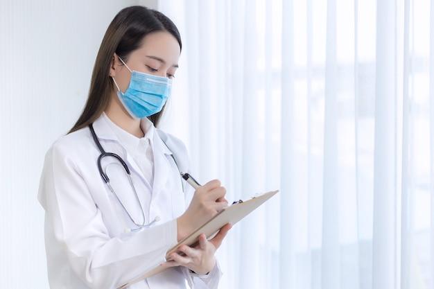 아시아 여성 의사는 병원에 있는 환자의 보고서를 보고 일합니다. 그녀는 코로나바이러스 전염병 상황에서 의료용 마스크를 착용합니다.