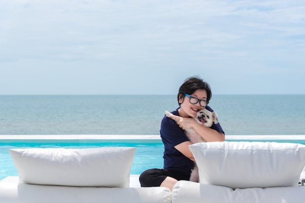Asian woman and dog hugging on white beach bed at swimming pool