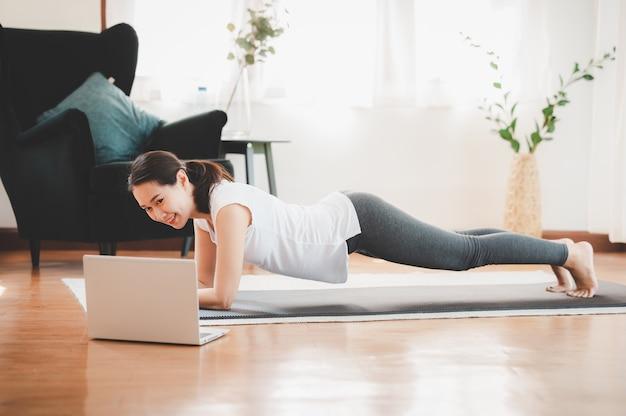 自宅のリビングルームで板運動をしているアジアの女性