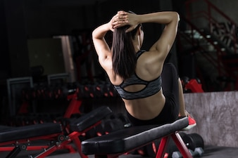 Asian woman doing sit-ups at gym, Abdominal exercises Sit up.