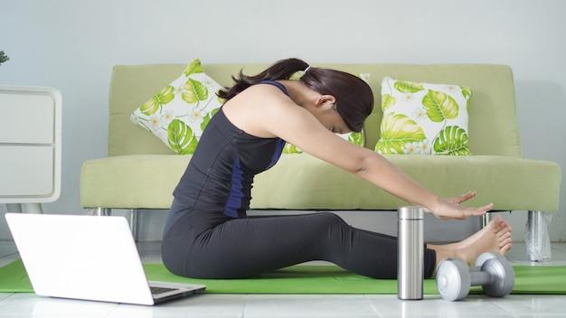 Азиатская женщина занимается йогой дома, разогреваясь, чтобы сгибаться