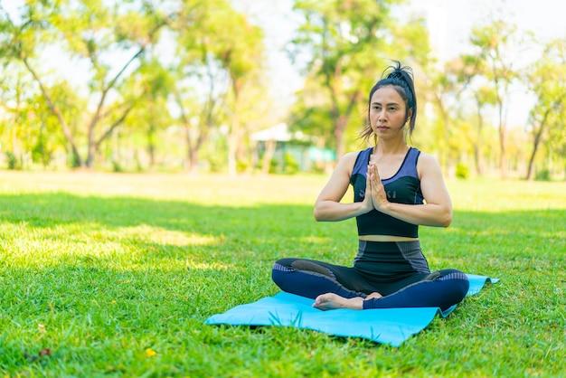 아시아 여자 요가 운동을 하 고 여름에 녹색 공원에서 운동복과 휴식