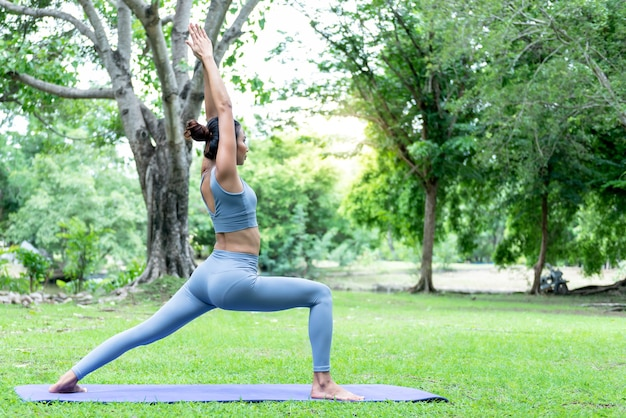 緑豊かな公園で、優雅な姿勢でヨガをしているアジアの女性