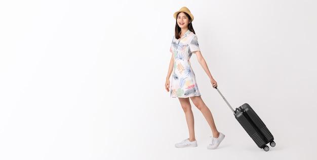 白い背景の上の茶色の帽子とスーツケースをドラッグするアジアの女性。