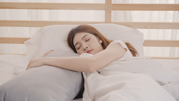 Asian woman dreaming while sleeping on bed in bedroom