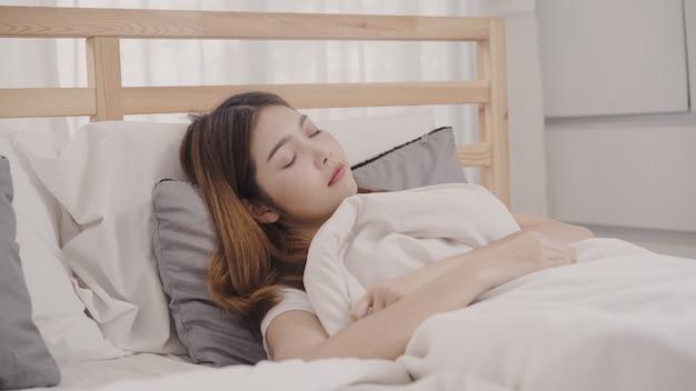 침실에서 침대에서 자고있는 동안 꿈꾸는 아시아 여자