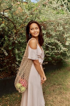 Asian woman in dress holding eco friendly mesh shopper bag with fresh tropical fruits.