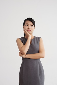 Asian woman in dress posing in studio, holding hand on cheek with pensive face expression