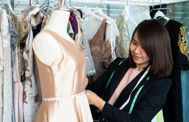 Азиатский модельер портнихи женщины измеряя размер манекена в выставочном зале.
