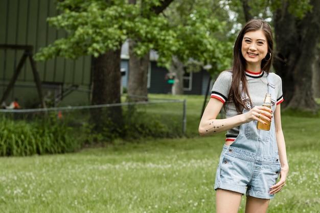 彼女の庭でビールを飲むアジアの女性