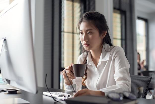 Азиатская женщина пьет кофе и портативный компьютер утром в офисе.