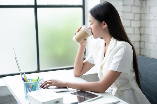 Азиатская женщина пьет кофе в офисе