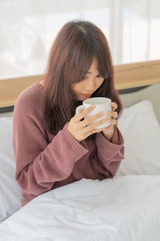 Asian woman drinking coffee on bed in the morning