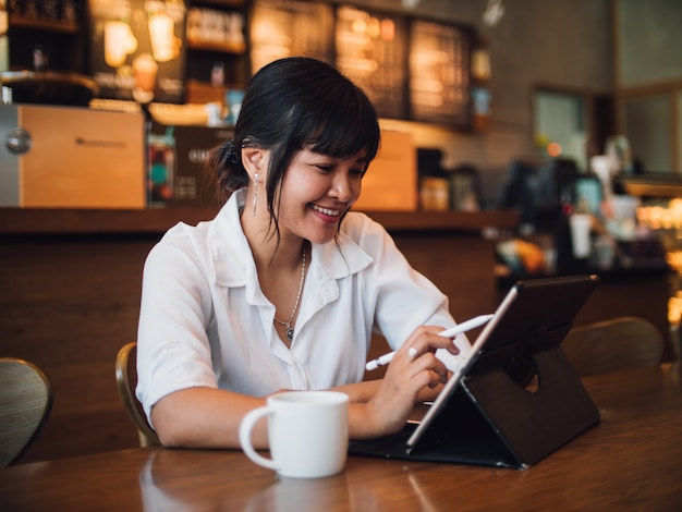 Asian woman drinking coffee in cafe and using laptop computer for working business