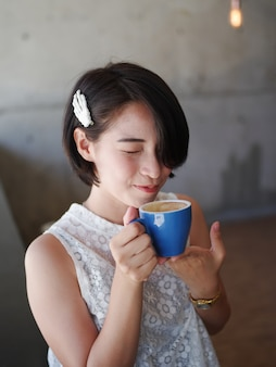 Asian woman drinking coffee in cafe