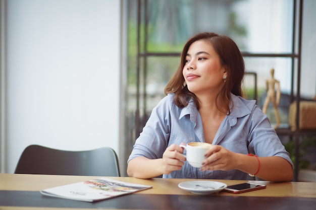 コーヒーショップカフェでコーヒーを飲みながら携帯電話を使用してアジアの女性