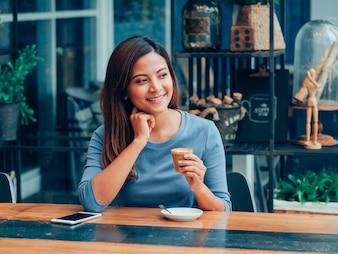 コーヒーショップカフェでコーヒーを飲むアジア人女性