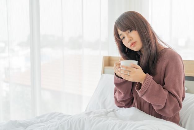 朝はベッドでコーヒーを飲みながらアジアの女性