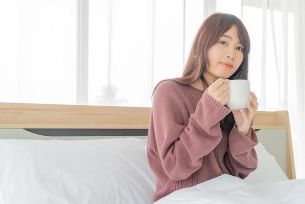 Азиатская женщина пьет кофе на кровати утром