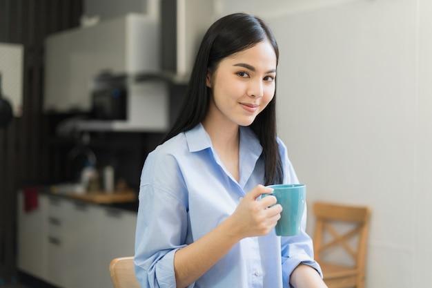 コーヒーを飲むアジアの女性は、午前中に家にいます。