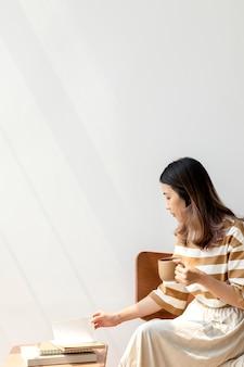 Donna asiatica che beve caffè mentre legge un libro a casa