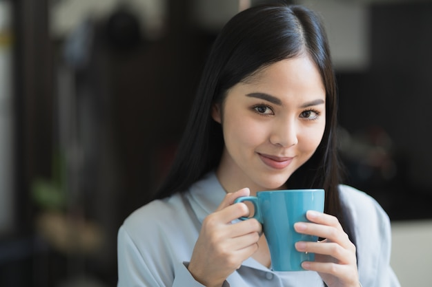 アジアの女性が家に滞在しながらコーヒーを飲む