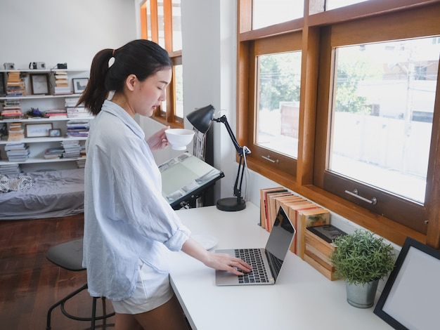 Asian woman drinking coffee in working room