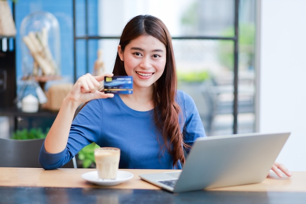 Asian woman drinking coffee and working with laptop computer