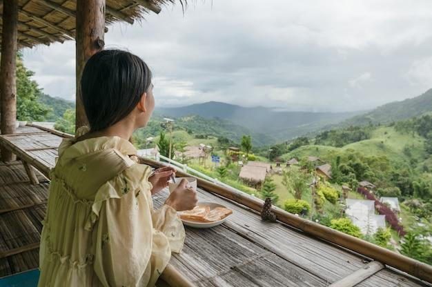ホットココア、トーストを飲み、休暇中にバルコニーで山の景色を眺めるアジアの女性