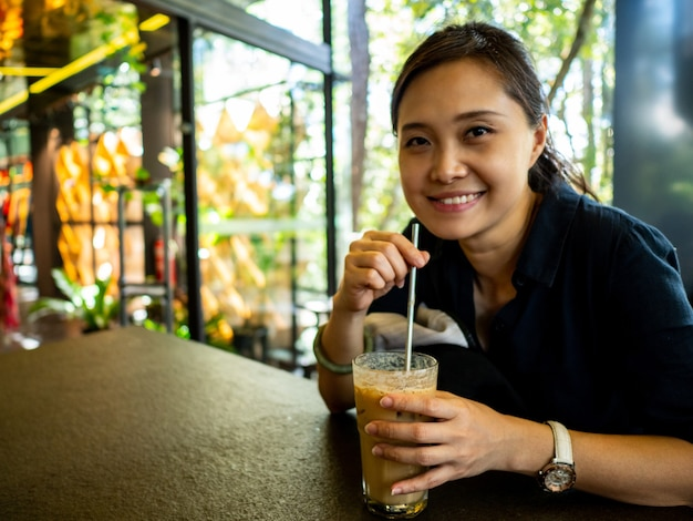 Asian woman drinking ice coffee  in restaurant