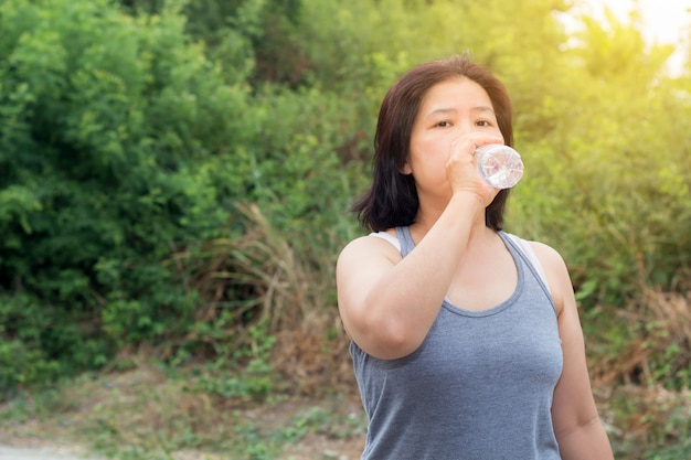Asian woman drinking water after sport exercise, sport woman holding bottle of pure water