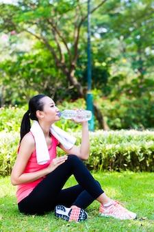 Азиатская женщина пьет воду после спорта в парке