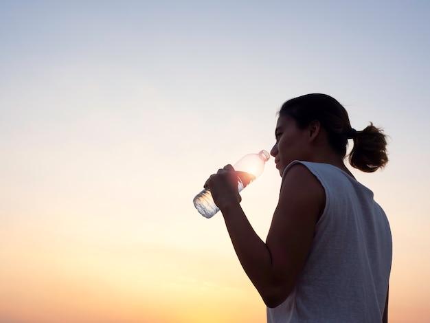 Азиатская женщина пьет воду из пластиковой бутылки после тренировки, тренируясь вечером летом на красивом закатном небе с копией пространства