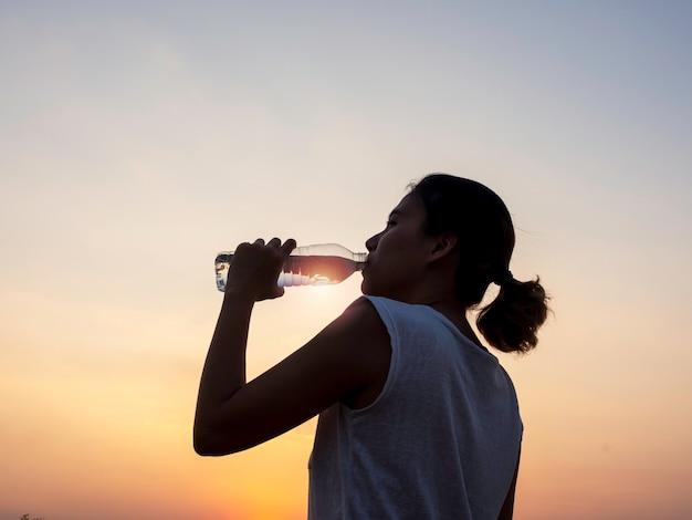Азиатская женщина пьет воду из пластиковой бутылки после тренировки, тренируясь вечером летом на красивом закатном небе
