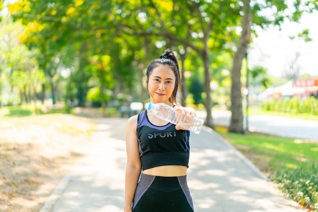 アジアの女性は公園で運動後のスポーツウェアで水を飲む