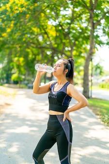 Азиатская женщина пьет воду в спортивной одежде после тренировки в парке