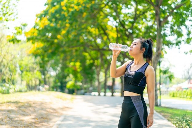 Asian woman drinking water in sportwear