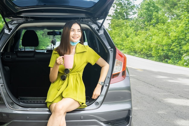Asian woman drinks coffee and travel alone during covid -19 pandemic