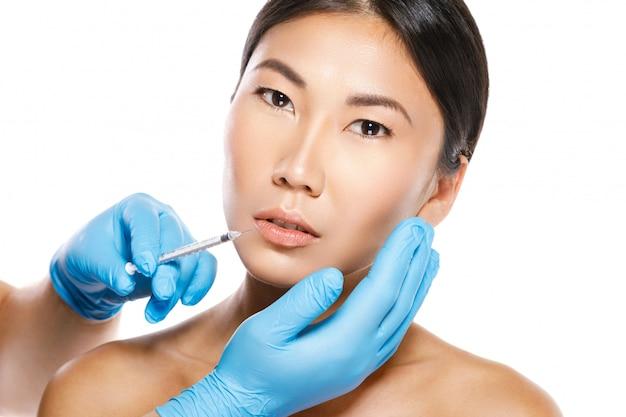 Asian woman during lips augmentation procedure.