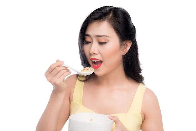 朝食にシリアルやミューズリーのボウルを食べるアジアの女性