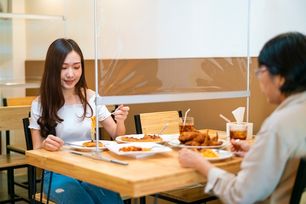 Asian woman eating food while siting separate and keep distance with table plastic shield partition in restaurant